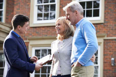 realtor shows mature couple around house for sale